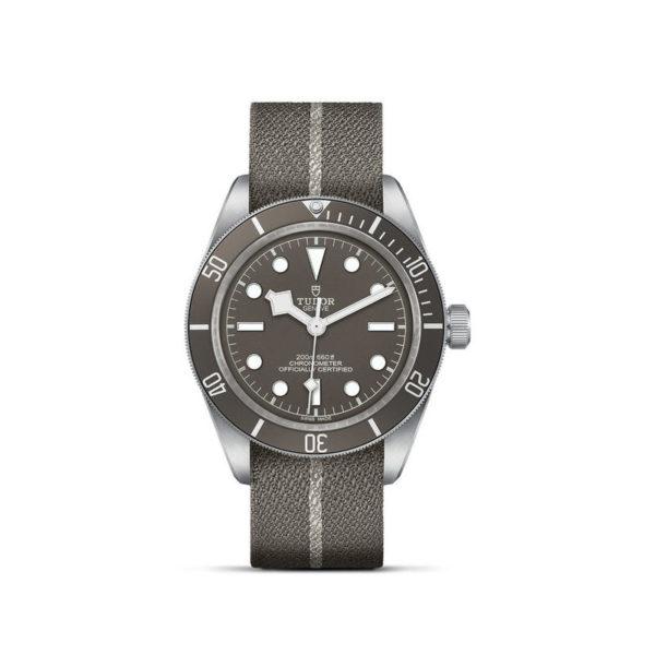Relógio TUDOR Black Bay Fifty-Eight com Caixa de 39mm prateada, bracelete em tecido castanho e cinzento. Disposição vertical, fundo branco.