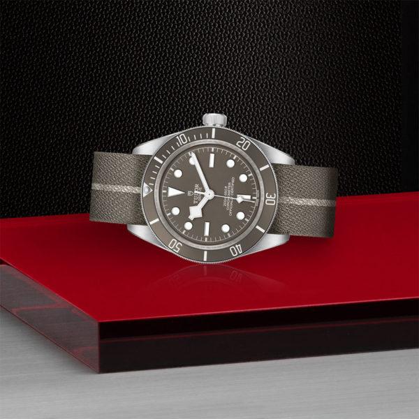 Relógio TUDOR Black Bay Fifty-Eight com Caixa de 39mm prateada, bracelete em tecido castanho e cinzento. Disposição de loja, deitado.