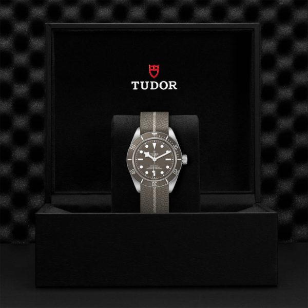 Relógio TUDOR Black Bay Fifty-Eight com Caixa de 39mm prateada, bracelete em tecido castanho e cinzento. Disposição em caixa de marca.